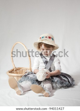 Young girl with a wicker basket on white background - stock photo
