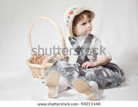 Young girl with a wicker basket on white background