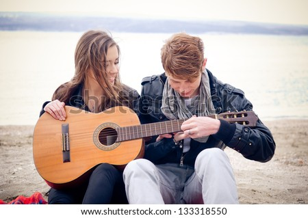 Young girl with acoustic guitar and her boyfriend on the beach - stock photo