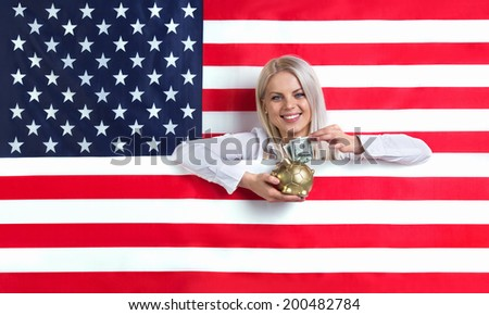 Young girl with an American flag and a piggy bank - stock photo