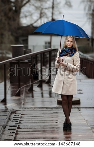 Young girl with an umbrella on a bridge in the rain - stock photo