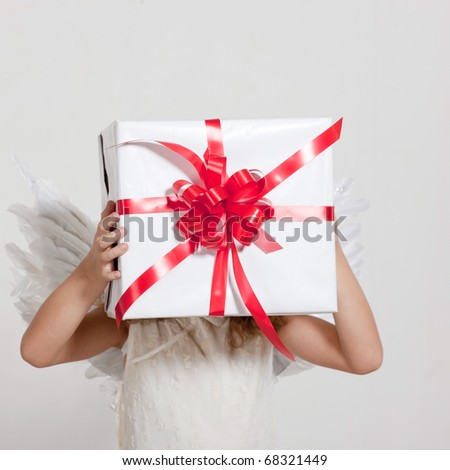 Young girl with angel wings and set of gifts in studio - stock photo