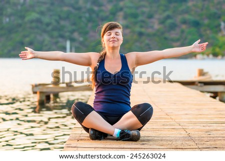 young girl with arms outstretched in the lotus position - stock photo