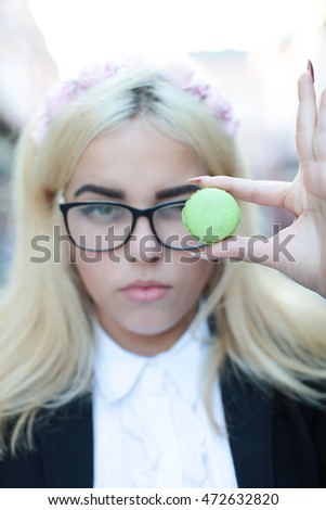 Young girl with attractive face fashion makeup blond hair holding green and  macarons