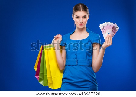 Young girl with bags and bunch of money in the hands on a blue background - stock photo