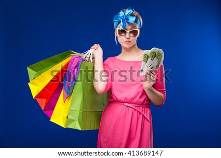 Young girl with bags and bunch of money in the hands on a blue background