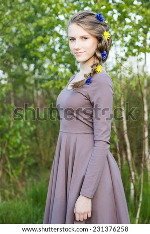 Young girl with beautiful hairstyle standing in park, half-length portrait  - stock photo
