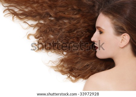 Young girl with beautiful long curly hair lying on white background