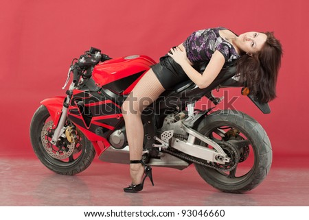 Young girl with bike, on red background - stock photo