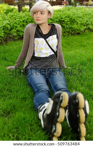 Young girl with black rollers in the park sitting on the grass