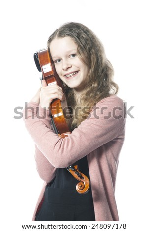 young girl with blond curly hair embraces violin in studio with white background - stock photo