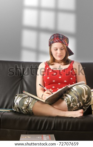 Young girl with blond hair is sitting at home on the couch and learn.