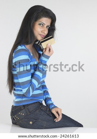 Young girl with blue t -shirt sitting on the table - stock photo