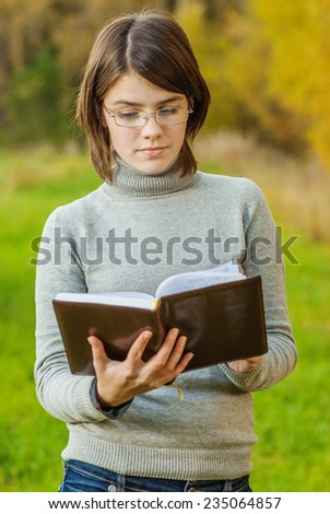 Young girl with book and glasses has reflected against an autumn field.