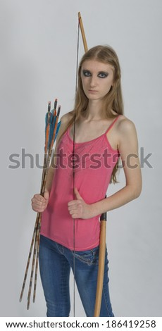 Young girl with bow and arrow  in a sports suit on a white background