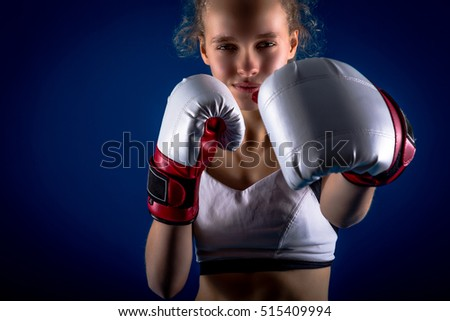 young girl with boxing gloves on dark blue background