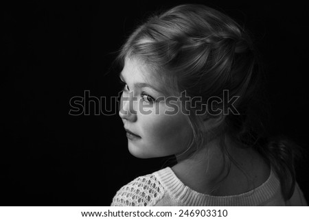 Young girl with braid in hair facing backward with head turned to side.