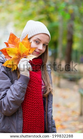 Young girl with bunch of autumn leaves outdoors