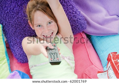 Young girl with chips in bed watching TV - stock photo