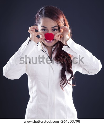 Young girl with clown nose on black background - stock photo