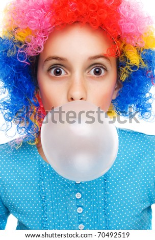 Young girl with clown wig and bubble gum isolated on white - stock photo