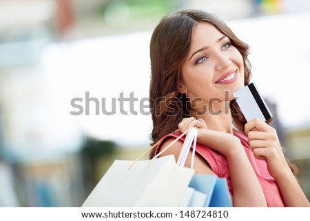 Young girl with credit card and shopping bags - stock photo