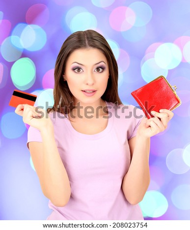 Young girl with credit card on bright background - stock photo