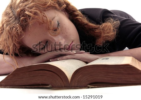 Young girl with curly red hair sleeping over old book