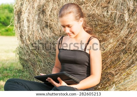 Young girl with  device siting  on the field close  to haystack