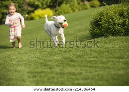 Young girl with dog playing in garden - stock photo