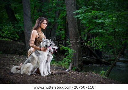 Young girl with dogs in forest