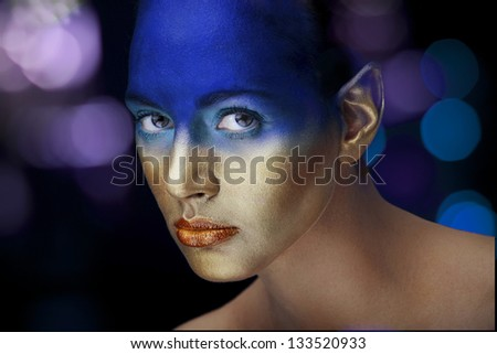 Young girl with elven ears with strong blue and golden makeup