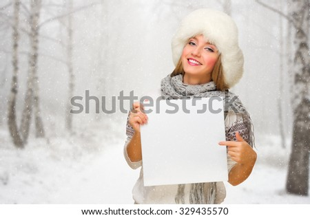 Young girl with empty card at snowy forest - stock photo