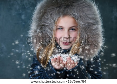 young girl with fleecy jacket blowing snow - stock photo