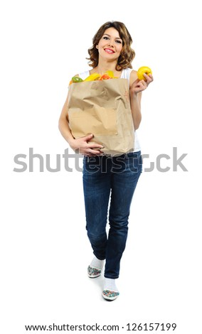 Young girl with fruits in paper bag isolated on white background