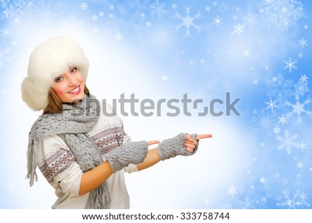 Young girl with fur hat showing pointing gesture on winter background - stock photo
