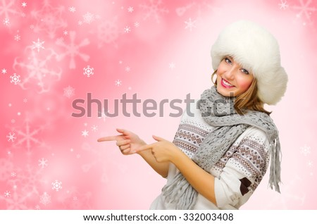 Young girl with fur hat shows pointing gesture on winter background - stock photo