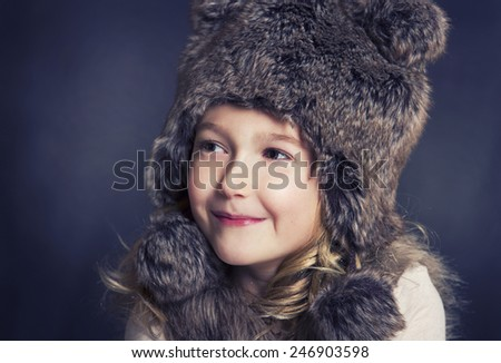 Young girl with fur winter hat, smiling and looking to the side - stock photo
