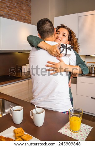 Young girl with gift box in the hands embracing to her boyfriend for a beautiful surprise while having breakfast on the home kitchen - stock photo