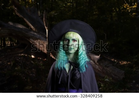 Young girl with green hair in suit of witch in forest. Halloween time
