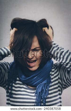 Young girl with hands on her head being desperate screaming - stock photo
