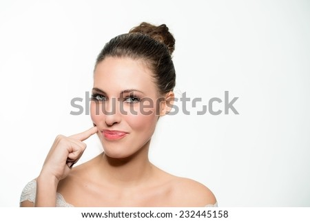Young girl with happy face expression standing with her finger raised to her cheek eyeing a yummy tasty treat with longing and a cute smile. - stock photo