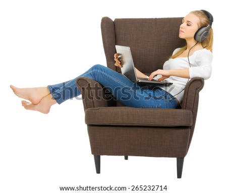 Young girl with headphones and laptop in chair isolated - stock photo