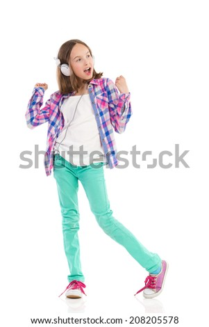 Young girl with headphones dancing and singing. Full length studio shot isolated on white.