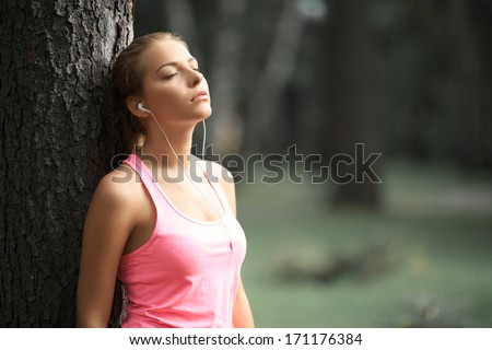 Young girl with headphones near tree