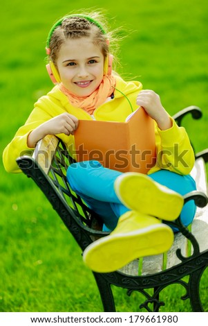 Young girl with headphones reading a book - stock photo