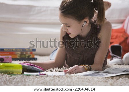 Young girl with headset doing homework on floor - stock photo