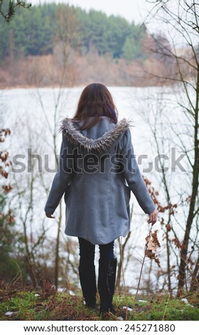 Young girl with her hair stands near the water in the cold season. Back view - stock photo