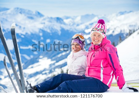 Young girl with her mother a ski outfit jumping in snow at winter outdoor in the Tirol, Austria - stock photo