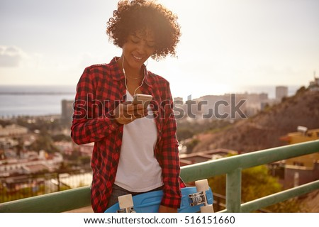 Young girl with her skateboard looking at cell phone wearing denim shorts, a white tank top and red and black shirt